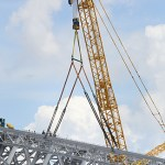 A crane lifts a section of steel into place connecting the ridge truss to the southern wall of the stadium.