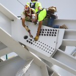 Workers bolt a section of steel to the ridge truss on the new Vikings stadium, which is nearly 60 percent complete. The Vikings said Friday they're adding another $5.9 million to the project.