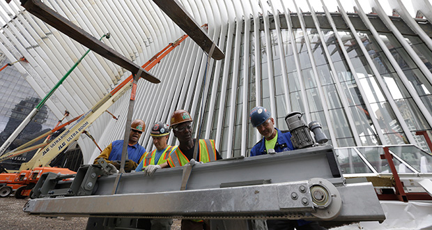 Construction workers secure a steel apparatus to a crane that will be used on the roof of the Oculus structure June 18 at the World Trade Center transportation hub, in New York. The Commerce Department reported Wednesday that construction spending increased 0.8 percent in May. (AP file photo)