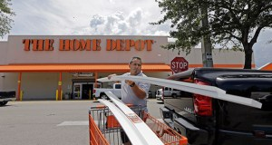 Vicente Aguiar loads garage door trims into his pickup truck July 13 outside a Home Depot in Hialeah, Florida. The Home Depot Inc. on Wednesday announced it is buying Interline Brands Inc., which distributes maintenance and repair products. (AP Photo: Alan Diaz)