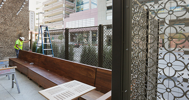 Workers put the finishing touches Wednesday on a fence outside an outdoor bar area at the Hotel Ivy, 201 S. 11th St., Minneapolis. (Staff photo: Bill Klotz)