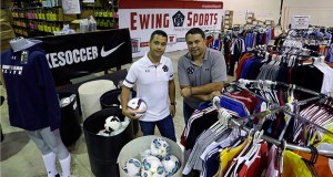 Chris Goodrich, left, and Les Korsos, pose July 29 with sale racks stocked with soccer uniforms and gear at a warehouse of their company, Ewing Sports, that sells mostly soccer uniforms to school and other teams, in Ewing, New Jersey. Key employees at the company, Goodrich and Korsos bought Ewing Sports from their retiring bosses in July. (AP Photo: Mel Evans)