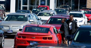 Customers check out a vehicle on the sales lot March 29 at a CarMax Inc. dealership in Brandywine, Maryland. Attitudes in September toward purchases of automobiles and other big-ticket items remained strong, especially among higher-income households, according to the University of Michigan's consumer sentiment report. (Bloomberg file photo)