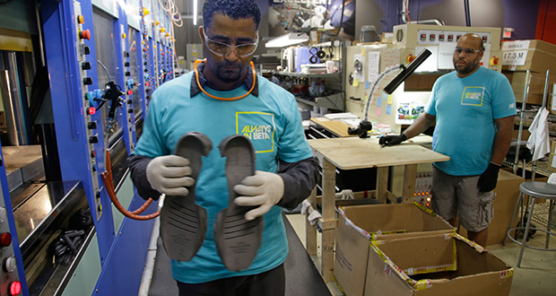 Joao Rodrigues, left, removes a pair of newly-formed midsoles July 1 for the New Balance 950v2 sneaker from an IMEVA oven as Loyd Johnson looks on at the company's manufacturing facility in Boston. The Labor Department reported Friday that producer prices were flat in August. (AP file photo)