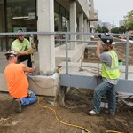 Workers install a railing on a footbridge over a rain garden on the Portland Ave side of the building. (Staff photo: Bill Klotz)