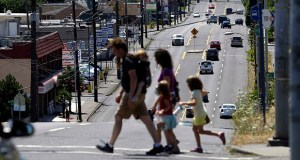 Pedestrians cross the wide swath of 82nd Avenue on July 14 in East Portland, Oregon. The Avenue is traditionally considered the dividing line between Portland and East Portland, where shabby apartment complexes, fading strip malls, wide avenues and fast-food chains are the norm.  AP file photo