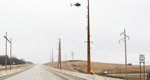 Crews use a helicopter to string wire between two transmission structures crossing Highway 52 near Zumbrota, Minnesota, for the CapX2020 Hampton-Rochester-La Crosse project. Submitted photo: Xcel Energy
