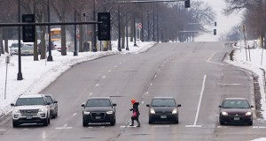 A woman crosses Olson Memorial Highway near the Harrison neighborhood in north Minneapolis on Wednesday. Harrison residents spoke Tuesday at a public hearing on a future light rail line to push for pedestrian safety on the highway and affordable housing. (Staff photo: Bill Klotz)
