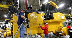 Rick Ring, left, and Corinne Schmitt-Bries attach a panel to a John Deere 1050K Crawler Dozer on Feb. 11, 2015, at John Deere Dubuque Works in Dubuque, Iowa. U.S. businesses reduced their stockpiles in November, as sales also slipped. ( AP file photo: Jessica Reilly/Telegraph Herald)