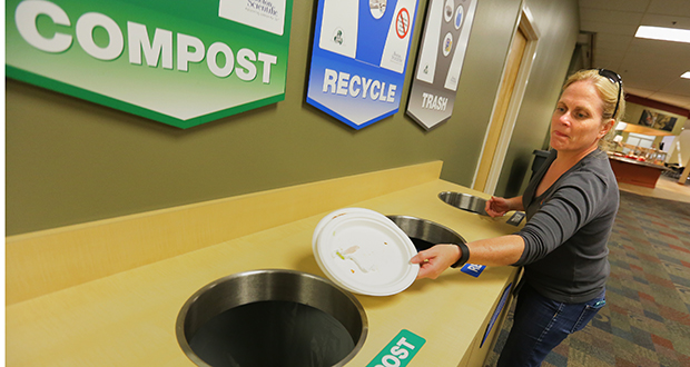 Sonia James, environmental specialist at Boston Scientific in Arden Hills, shows how colorful signs inform employees which items should go into the bins for compost, trash and single-source recycling. Boston Scientific revised its waste-management program last year, before it became mandatory for commercial property owners on Jan. 1. File photo: Bill Klotz