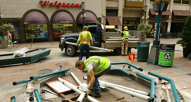 Workers take apart a bus shelter along Nicollet Mall in downtown Minneapolis last summer. Metro Transit will build 12 new bus shelters along the reconstructed mall. File photo: Bill Klotz