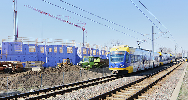 A Blue Line train runs by the 135-unit affordable housing project under construction near the Lake Street Station in Minneapolis. St. Paul-based Wellington Management says transit access played a major role in selecting the site for its project. Staff photo: Bill Klotz