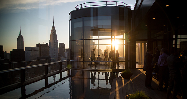 Guests attend a pool party June 7 in the penthouse apartment at the 50 United Nations Plaza building in New York. About 3,574 newly built apartments will reach the market in 2016, according to brokerage Corcoran Sunshine Marketing Group. (Bloomberg photo: Michael Nagle)