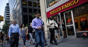 Pedestrians pass in front of a Wells Fargo & Co. bank branch July 12 in New York. Wells Fargo announced it is cutting its sales goals for retail bankers in the wake of being fined $185 million by state and federal regulators. (Bloomberg file photo)