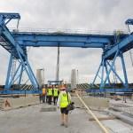 Members of the press walk through one several segment lifting machines still on the bridge deck.