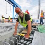 Ironworkers installing stainless steel rebar.