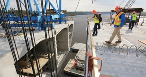 Visitors at the St. Croix Crossing project site look down at a gap in the bridge deck. The gap was about to be filled by concrete segments delivered to the site by river barge. (Staff photo: Bill Klotz)