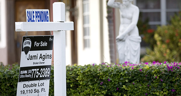 "A ""Sale Pending"" placard is placed atop a realty sign Jan. 8, 2015, outside a home for sale in Surfside, Florida. The National Association of Realtors reported Thursday that pending home sales rose in the South and West in September. (AP file photo)"