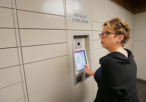 The solution to the growth in package deliveries to apartment buildings may be in new automated locker systems. Bloomington-based Doran Cos. is using the Package Concierge system at The Moline at 100 Eighth Ave. S. in Hopkins and all of its other new apartment developments. Alison Guthrie, the property manager at the Moline, demonstrates how to use the system. (Staff photo: Bill Klotz)
