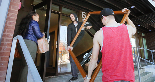 Local musicians Ryan Matheson, right, and Robbie Sims move furniture into a first-floor two bedroom apartment in the Hawthorne EcoVillage Apartments at 617 Lowry Ave. N. in Minneapolis. (Staff photo: Bill Klotz)