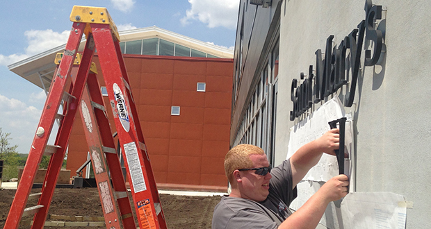 A worker adds the final touches to the lettering for St. Mary's University of Minnesota's new wing at institution's Cascade Meadow Wetlands & Environmental Science Center, at 2900 19th St. NW in Rochester. (Photo: Anne Bretts)