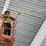 A worker applies white paint to the steel canopy.(Staff photo: Bill Klotz)