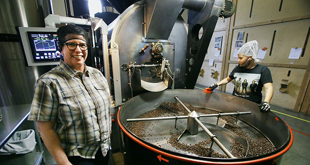 """Peace Coffee CEO Lee Wallace (right) pauses to chat with production roaster Stormey Charette in the company's roastery in south Minneapolis. Peace Coffee is one of 17 certified """"B Corporations"""" in Minnesota, which """"meet rigorous standards of social and/or environmental performance, accountability and transparency."""" (Staff photo: Bill Klotz)"""