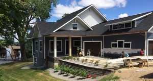 Workers from JMS Custom Homes are completing final details at newly sold home at 17300 County Road 101 in Minnetonka. Designers tweaked the plans for a four-car garage to fit three bays on the main level — and tuck a fourth into the lower lakefront level to handle outdoor furniture, canoes and other outdoor gear. (Photo: Anne Bretts)