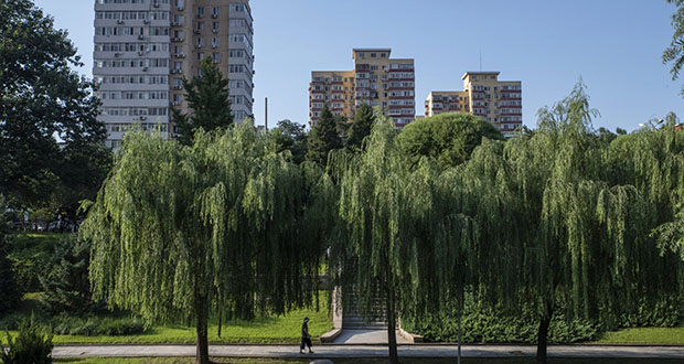 China's legislature is making enacting a property tax a high priority, with the hope it will help stabilize residential property speculation. In this July 26 photo, a man walks past willow trees at a park as residential buildings stand in the background in Beijing. (Bloomberg file photo)