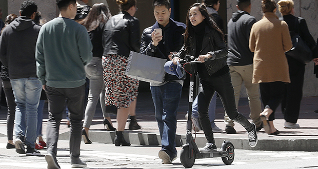 An increasing number of U.S. cities are trying to adapt to a world where more people use vehicles such as scooters and bikes in place of cars. In this April 17 photo, a woman rides a motorized scooter through a crosswalk in San Francisco. (AP file photo)