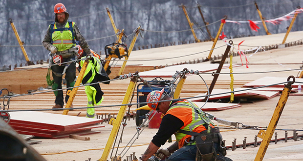 Construction workers rebuild the deck of the High Bridge in St. Paul in March 2018. The industry is having an unusually strong winter, in part because of mild weather that kept more workers on the job into December. (File photo: Bill Klotz)