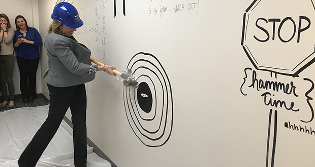 Media Minefield CEO Kristi Piehl takes the first swings Thursday to enlarge the company's office at 10590 Wayzata Blvd. in Minnetonka. The company has grown from one worker to 27 since Piehl founded it in 2010. (Submitted photo: Media Minefield)