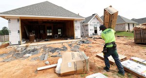 A worker carries supplies for a new house June 19 in Brandon, Mississippi. Sales of new homes increased 4.9% in the South in May, the Commerce Department said Tuesday. (AP Photo: Rogelio V. Solis)