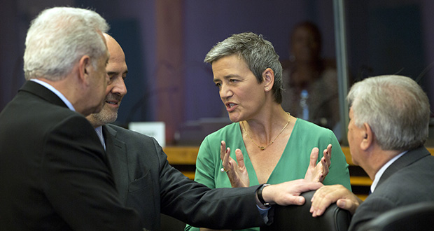 European Commissioner for Competition Margrethe Vestager, center, speaks with European Commissioner for Economic and Financial Affairs Pierre Moscovici, second left, and European Commissioner for Migration and Home Affairs Dimitris Avramopoulos, left, during the weekly college meeting at EU headquarters Wednesday in Brussels. (AP photo)