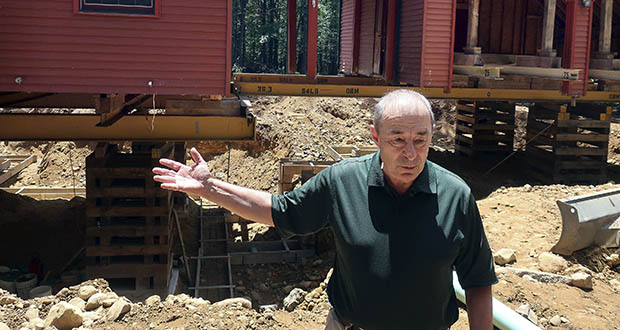 "Peter Brenn gestures toward his raised house July 1 in Willington, Connecticut. The concrete foundation of his home is being replaced with money from a state grant program. The foundation had been deteriorating due to the presence of an iron sulfide known as pyrrhotite, often described as ""a slow-moving disaster,"" which causes concrete to crack and break gradually as it becomes exposed to water and oxygen. (AP Photo: Ted Shaffrey)"