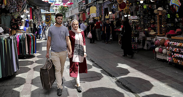Newly married Iranian couple, Mohammad Davoodi, 28, and his wife Mahsa Asadzadeh, 20, walk in a shopping center July 3 in downtown Tehran, Iran. Iran's large middle class has been hit hard by the fallout from unprecedented U.S. sanctions, including the collapse of the national currency. Perhaps most devastating has been the doubling of housing prices. More newlyweds move in with their families to save money. (AP Photo: Ebrahim Noroozi)
