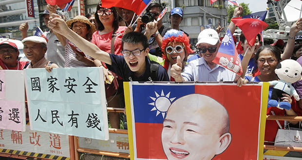 """Supporters of Kaohsiung Mayor Han Kuo-yu celebrate Monday in Taipei, Taiwan, after he won the nomination of the Nationalist Party for the coming presidential election. The placard reads """"Nation safe, people rich!"""" (AP photo)"""
