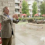 Doran Cos. founder Kelly Doran explains the function of the centralized amenity courtyard at The Reserve at Arbor Lakes during a tour of the apartment complex. (Staff photo: Matt M. Johnson)