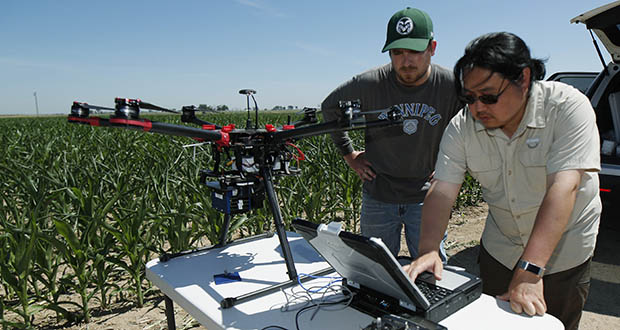 U.S. Department of Agriculture intern Alex Olsen, left, and engineering technician Kevin Yemoto work to set up a drone July 11 for flight over a research farm northeast of Greeley, Colorado. Researchers are using drones carrying imaging cameras over the fields in conjunction with stationary sensors connected to the internet to chart the growth of crops in an effort to integrate new technology into the age-old skill of farming. (AP Photo: David Zalubowski)