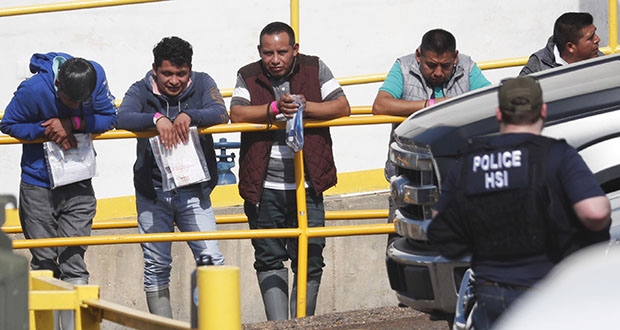 Handcuffed workers await transportation to a processing center following a raid Wednesday by U.S. immigration officials at Koch Foods Inc., plant in Morton, Mississippi. (AP photo)