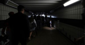People walk in near darkness at Clapham Junction station during a power cut, in London on Aug. 9. London and large chunk of the U.K. were hit with a power outage that disrupted train travel and snarled rush-hour traffic. (AP file photo)