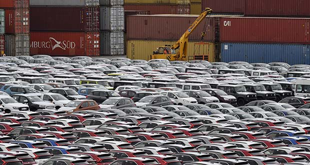 German big-name companies from Siemens to Daimler have issued warnings about pressure on sales and political uncertainty. In this May 16 photo, cars for export and import are stored in front of containers at the harbor in Bremerhaven, Germany. (AP file photo)