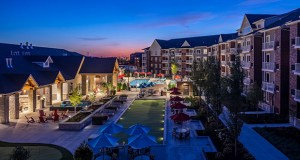 The first completed apartment building at The Reserve at Arbor Lakes forms an amenity courtyard with the complex's clubhouse. (Submitted photo: Doran Cos.)