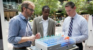 Aaron Mullins, left, an architect with HGA Architects, explains the features of an interior model of the Douglas Dayton YMCA in Gaviidae Common to YMCA Vice President of Operations Kerry Givens, center, and attendee Jason Clochie at the 2018 Building Community Exhibition in the IDS Center's Crystal Court. (File photo: Matt M. Johnson)
