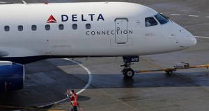 For the quarter ended Sept. 30, Delta earned about $173 million more than in the same period last year. In this Feb. 5 photo, a ramp worker guides a Delta Air Lines plane at Seattle-Tacoma International Airport in Seattle. (AP file photo)