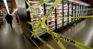 In this Oct. 31, 2019, file photo, a customer walks past the off-limits frozen foods section of Big John's Market in Healdsburg, Calif., shortly after it reopened and power was restored after being turned off for four days in an attempt to stem fires caused by wind-damaged power lines. (AP Photo/Charlie Riedel, File)