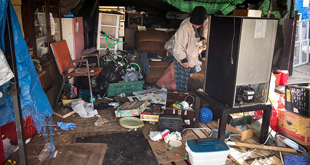 A person looks trough items Nov. 12 in a home at a homeless encampment in Oakland, California, on Tuesday. Statewide, about a quarter of California's 130,000 homeless suffer from severe mental illness. (Bloomberg photo: David Paul Morris)