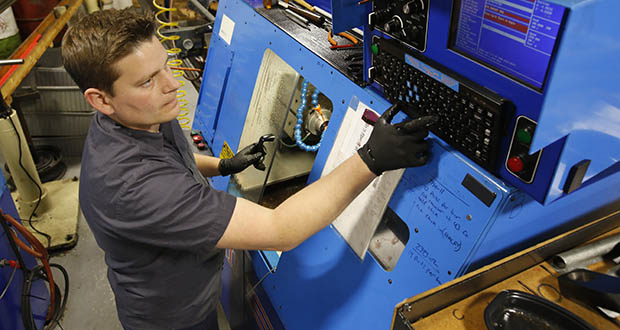 Kyle Chittock sets up a computerized lathe Nov. 11 at his family's manufacturing business, Simple Country, in Grass Valley, California. (AP photo)