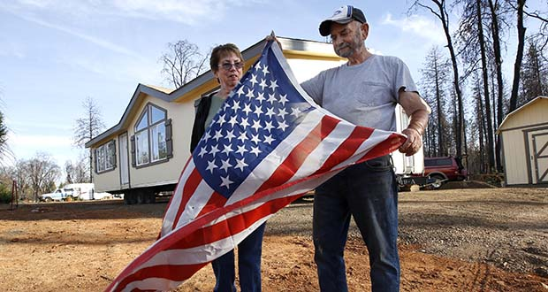 Joyce and Jerry McLean unfurl an American flag Tuesday outside their new modular home that was recently moved in to replace their home that was destroyed by last year's Camp Fire, in Paradise, California. The McLean's home is one of nearly 9,000 Paradise homes destroyed in the deadliest and most destructive wildfire in California history. Days after the fire Jerry McLean found the flag still flying in front of the burned out remains of the couple's home. (AP Photo: Rich Pedroncelli)