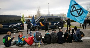 Police watch as activists from the international group called Extinction Rebellion sit blocking the street during a protest against climate change outside the COP25 Climate summit in Madrid, Spain, Monday, Dec. 9, 2019. A global U.N.sponsored climate change conference is taking place in Madrid. (AP Photo/Andrea Comas)